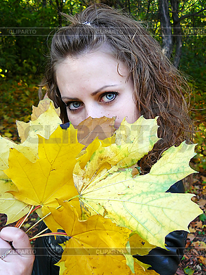 Brown-haired woman holds yellow leaves in hand | High resolution stock photo |ID 3054499