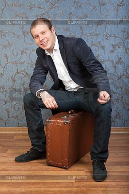 Młody mężczyzna siedzi na starej brązowej walizce | Foto stockowe wysokiej rozdzielczości |ID 3344746