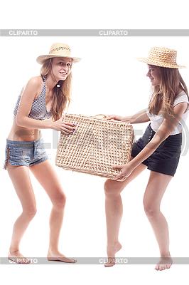Dwie dziewczyny w słomianych kapeluszach z walizką słomy | Foto stockowe wysokiej rozdzielczości |ID 3107652