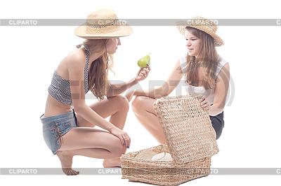Dwie dziewczyny w słomianych kapeluszach z walizką słomy | Foto stockowe wysokiej rozdzielczości |ID 3107654