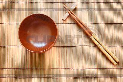 Палочки для еды с деревянной чашкой на бамбуковой циновке | Фото большого размера |ID 3110681