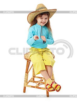 Kleines Mädchen in Strohhut sitzt auf hölzernen Stuhl | Foto mit hoher Auflösung |ID 3145614