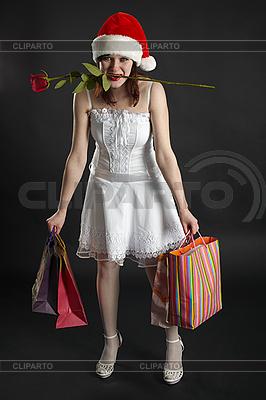 Amüsant Mädchen im Weihnachts-Mütze, mit Käufen und stieg | Foto mit hoher Auflösung |ID 3146460