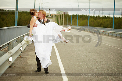Groom carries his bride in his arms on bridge | High resolution stock photo |ID 3147527