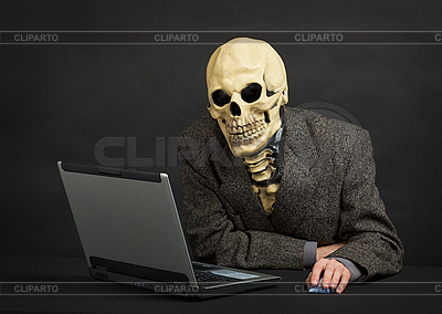Terrible skeleton sits at black office with laptop | Foto stockowe wysokiej rozdzielczości |ID 3148779