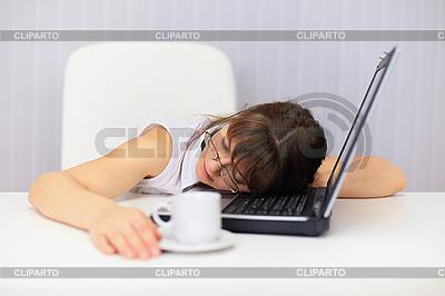 Młoda kobieta komicznie śpi na laptopie w biurze | Foto stockowe wysokiej rozdzielczości |ID 3156480