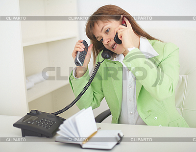 Young woman - secretary speaks by several phones simultaneously | Foto stockowe wysokiej rozdzielczości |ID 3159761