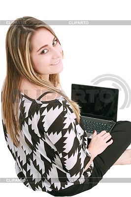 Happy young woman using laptop while sittingg on floor | Foto stockowe wysokiej rozdzielczości |ID 3361417